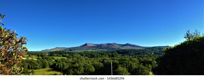 Blue sky over a distant view of Cadair Idris / Cader Idris mountain in Gwynedd, Wales, at southern end of the Snowdonia National Park near the town of Dolgellau. June 2014.