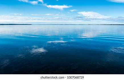 blue sky reflected in calm water with ripples