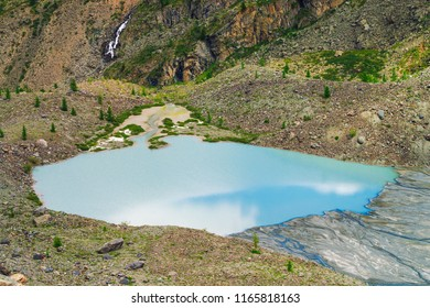 Blue sky reflected on beautiful lake near stone slope of mountain. Waterfall on mountainside. Azure surface of water. White sand and big stones on shore. Unusual landscape of Altai nature.