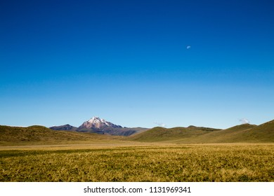 Blue sky with small moon and Andean mountains at the base