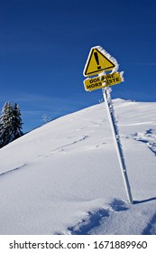 Blue sky and snow with an ice-covered yellow warning triangle sign in French saying Domaine Hors Piste or Off-Piste area.
