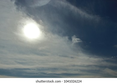 Blue Sky with soft clouds and the sun behind