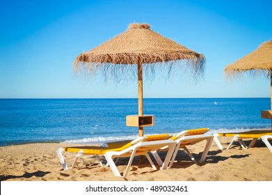 Blue sky and straw umbrella on a beautiful tropical beach background