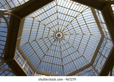 Blue sky and sun gleaming through greenhouse/orangery roof