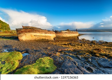 Blue sky and sunshine over old abandoned fishing boats at Salen on the Isle of Mull in Scotland