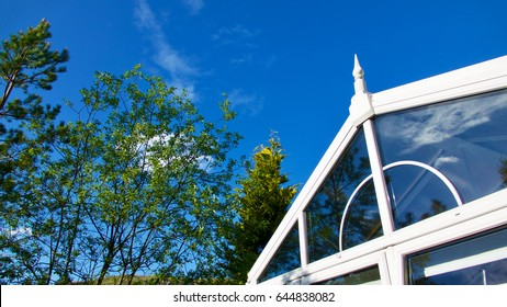Blue sky, trees and clouds reflected in a garden conservatory.