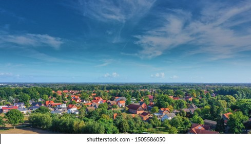 Blue sky with veil clouds over the houses at the edge of a suburb in Germany, aerial photo