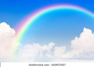 Blue sky and white cloud and rainbow. A bright rainbow background.