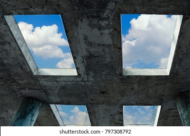 A blue sky with white clouds can be seen through the windows in a concrete building. The concept of faith, freedom and hope.