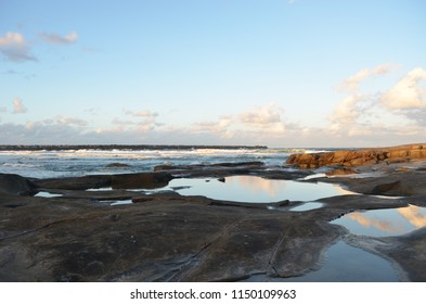 A blue sky with white clouds is changing colour at sunset and is reflected in rockpools. Some of the rocks are dark, others are golden in the light. Waves are breaking, and a breakwater can be seen.
