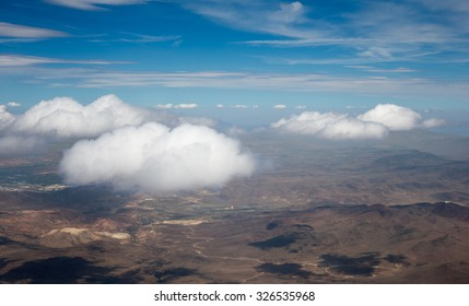 Blue Sky, White Clouds, Desert Floor - Desert floor viewed from an airplane.  Bright blue sky, fluffy white clouds, and Nevada's dry, desert terrain shown below.  Photographed near Reno, Nevada.