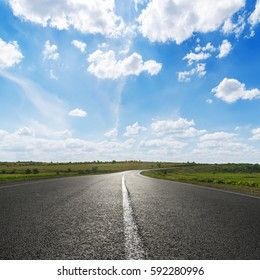 blue sky with white clouds over asphalt road