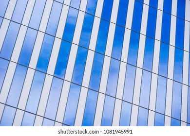 Blue sky and white clouds reflected in the glass and metal of a modern architectural highrise.