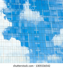 Blue sky and white clouds reflection on glass facade of a modern office building