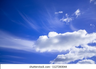 Blue sky with white fluffy clouds on bright sunny day