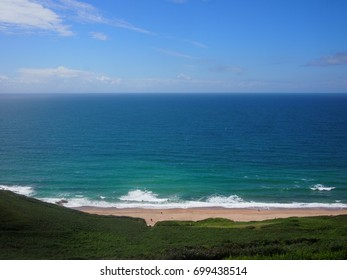 Blue sky, white sand, and turquoise sea at Praa Sands beach in Cornwall.