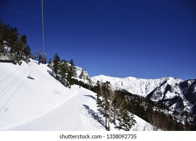 Blue sky and white snowy mountain. Ski lift to the top of the ski resort. Gunma. Japan