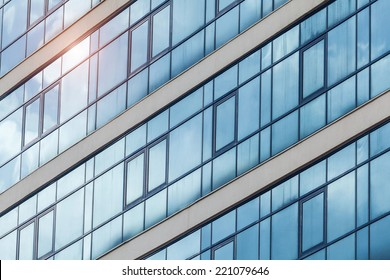Blue skyscraper facade. In a window the sun is reflected.
