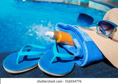 Blue slippers with sunscreen cream, towel, straw hat and sunglasses on border of a swimming pool - holiday tropical concept