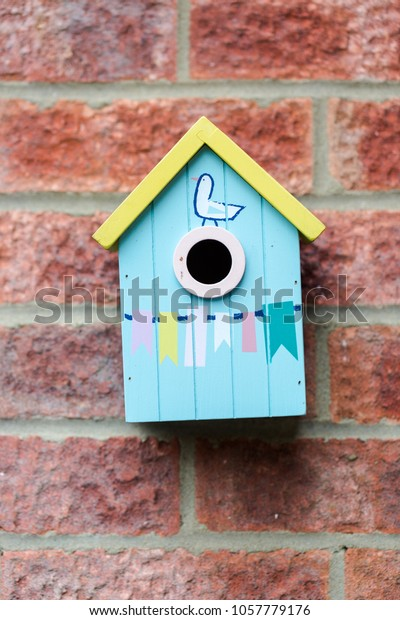 Blue small cue wooden bird house, hand painted with ornaments and bird, hanged on brick wall. Close up vertical shot