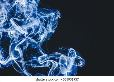 Blue smoke forming shapes on black background.