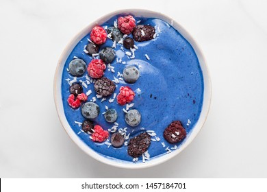 blue smoothie bowl with fresh and frozen berries, banana and coconut on white marble table. healthy breakfast. top view