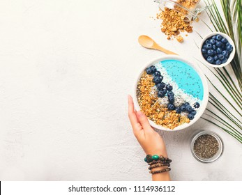 Blue smothie in bowl with granola and berries, holding hand on white background