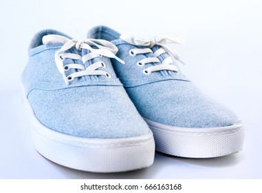 Blue sneaker on a white background. Cyan classic sneakers with white laces on a white rubber sole on white background. Sports, city footwear.