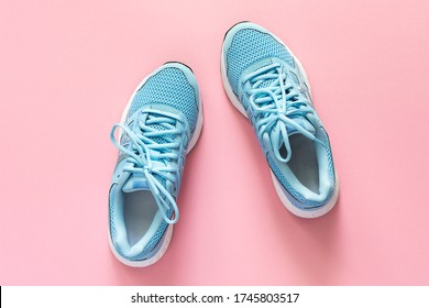 Blue sneakers isolated on a pink background, seasonal shoes for walking and sports, copy space, top view