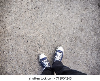 Blue sneakers on asphalt road. Space for editorial use.
