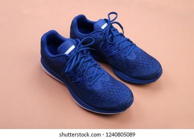 Blue sneakers on orange pastel background