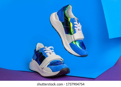 Blue sneakers on blue and pink background. Creative sport footwear design concept. Women or teenager glamorous shoes. One shoe flying in the air.