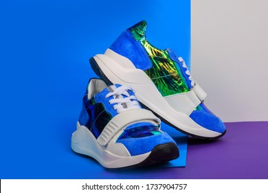 Blue sneakers on blue and pink background. Creative sport footwear design concept. Women or teenager glamorous shoes.