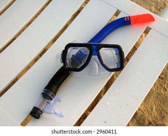 A blue Snorkel and face mask sitting on a beach lounge chair