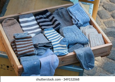 blue sock in wood tray ,woman's sock and pile of clothes in open drawer, warm winter , cloth shop