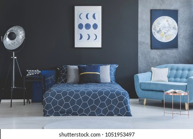 Blue sofa in bedroom interior with navy blue bed against dark wall with gallery of posters