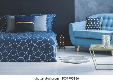 Blue sofa with patterned cushion and grey fur next to a dark bed in cozy bedroom interior with table