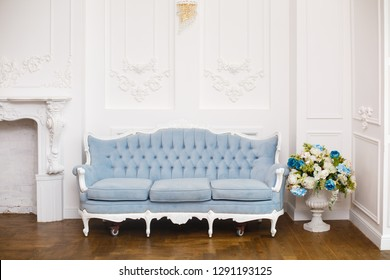 Blue soft sofa in light interior with fabric upholstery. Elegant royal luxury interior with white walls and blue sofa