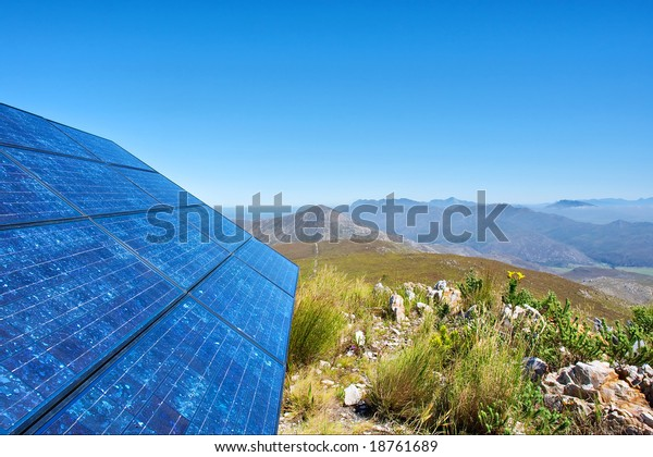 Blue solar batter cells and awesome mountain landscape as a background. Shot in Salmonsdam Nature Reserve, near Hermanus/Stanford, Western Cape, South Africa.