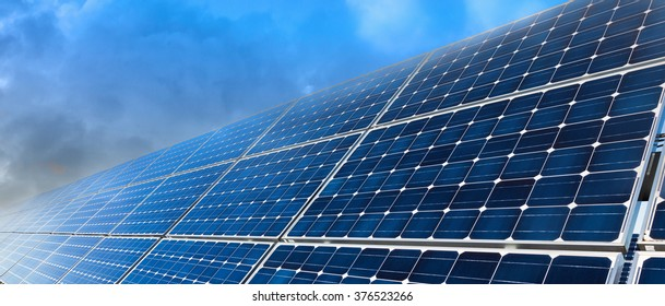 Blue solar panels and cloudy sky, panoramic background