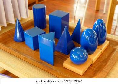 Blue solid wood shapes to study geometry and volumes, cones, triangles, squares, spheres on a wooden tray. Materials of the Primary Montessori classroom.