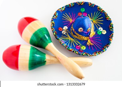 Blue sombrero with colorful ornaments on white background next to pair of maracas pained with the colors of the Mexican flag/Cinco de Mayo concept