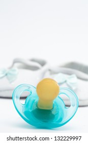 Blue soother in front of baby booties on white background
