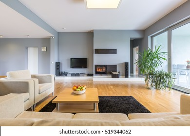 Blue and spacious room with couch and plasma television