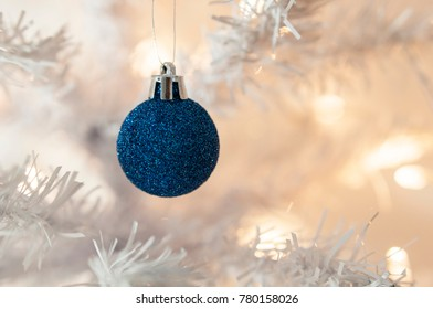 Blue sparkling ball on white Christmas tree, copy space, selective focus