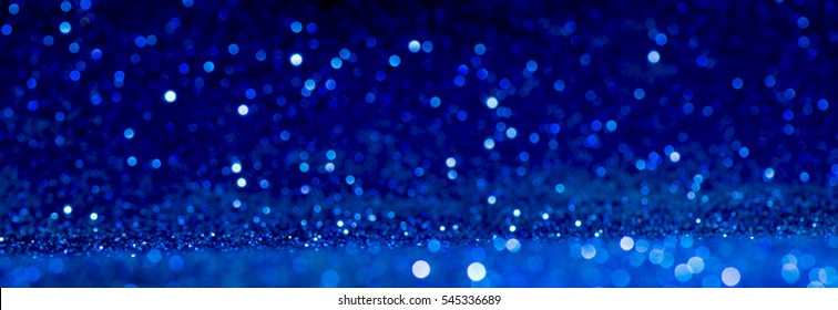 blue Sparkling Lights Festive background with texture. Abstract Christmas twinkled bright bokeh defocused and Falling stars. Winter Card or invitation.