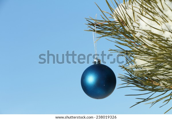 The blue sphere hanging on a Christmas tree against the sky