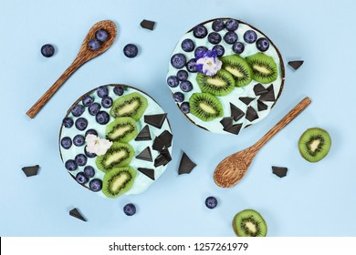 Blue spirulina and berry smoothie bowl, fresh blueberries, kiwi and chocolate pieces with wooden spoons served in coconut bowls over a blue background. Image shot from above / overhead.