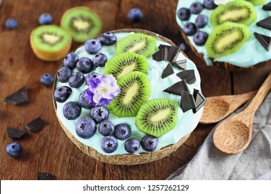 Blue spirulina and berry smoothie bowl, fresh blueberries, kiwi and chocolate pieces with wooden spoons served in coconut bowls over a rustic background. Image shot from above / overhead.