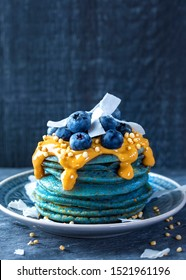 Blue spirulina pancakes topped with peanut butter, blueberries and coconut chips
